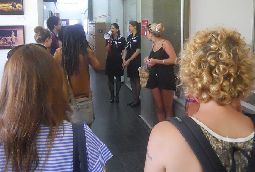 אנשים עומדים במסדרון, אלה סלומון במדי דיללת עם מגפון ואנשים עומדים ומסתכלים