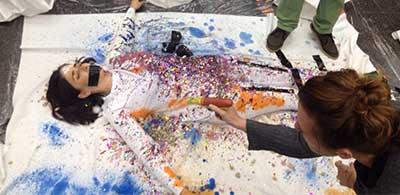 מיצג סלפי עם אלה סלומון כשאשר אנשים משתפים פעולה ומרססים צבע על בגדיה והסדין